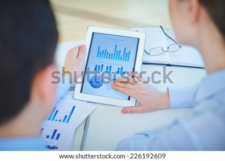 Close-up of business document in touchpad being analyzed by two co-workers