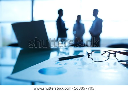 Close-up of business document, pen and eyeglasses at workplace on background of office workers interacting - stock photo