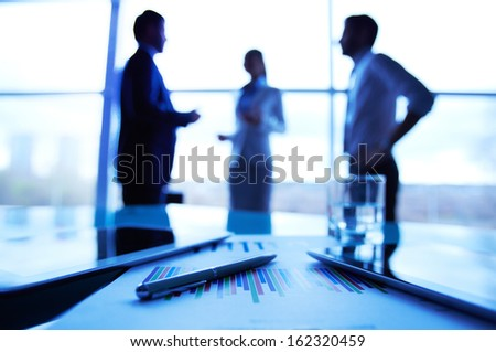 Close-up of business document, pen, glass of water and touchpads at workplace on background of office workers interacting - stock photo