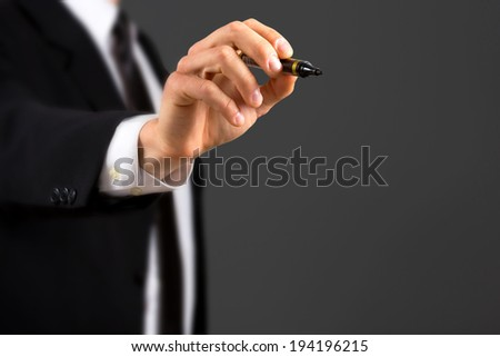Close up of business dressed male hand holding marker,isolated on dark background.