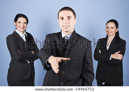 Close up of business group smiling with a businessman in front of image giving welcome gesture and his colleagues women standing with hands crossed and smiling in background - stock photo