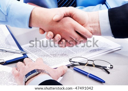 Close-up of business handshake over workplace with documents, pens, glasses - stock photo