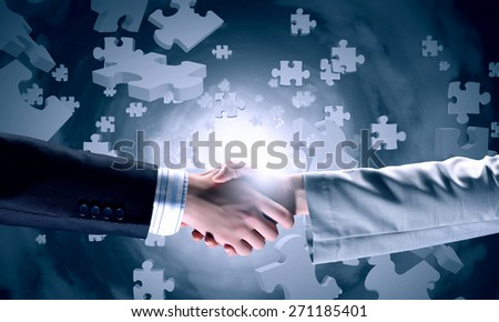 Close up of business handshake with puzzle elements at background - stock photo