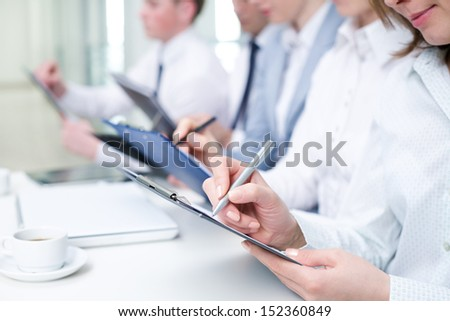 Close-up of business human hands writing in paper - stock photo