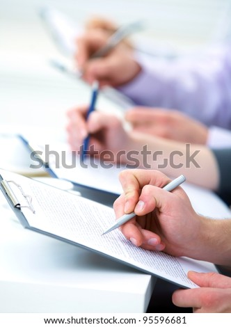 Close-up of business human hands writing in paper