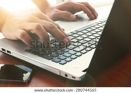 Close up of business man hand working on laptop computer on wooden desk as concept with overcast effect - stock photo