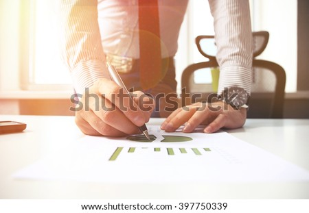 close up of business man hand working on laptop computer with business graph information diagram on wooden desk as concept