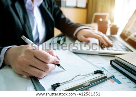 close up of business man hand working on laptop computer with business graph information diagram on office desk as concept in morning light