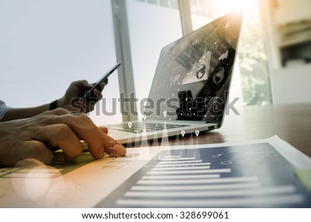 close up of business man hand working on laptop computer with digital layer business graph information diagram on wooden desk as concept