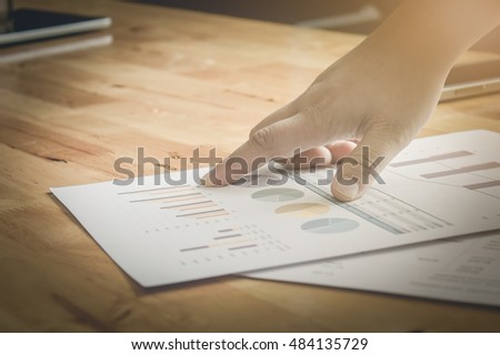 Close-up of business man hands pointing at turnover graph while discussing it