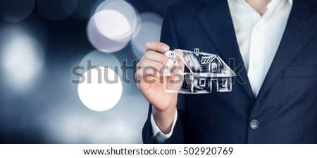close up of business man holding small house in his hands