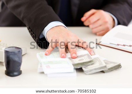 Close-up of business man's hand  giving money packs - stock photo