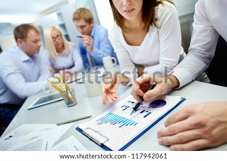 Close-up of business partners hands over document with their colleagues working on background - stock photo