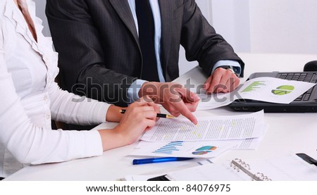 Close-up of business partners hands over papers discussing them - stock photo