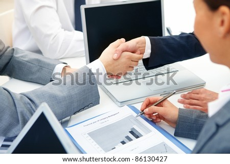 Close-up of business partners handshaking in working environment - stock photo