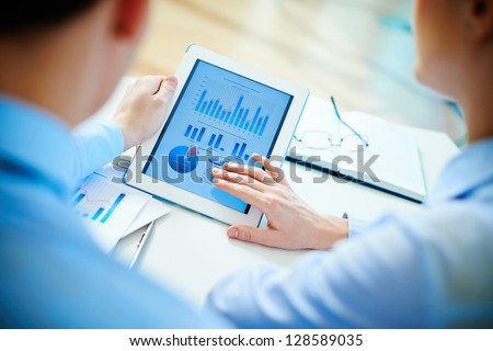 Close-up of business partners looking at business document in touchpad - stock photo