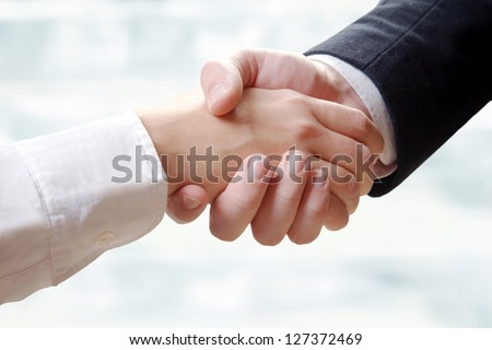 Close- up of business partners making handshake - stock photo