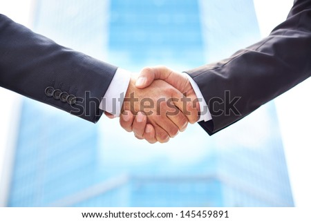 Close-up of business partners shaking hands to do business together - stock photo