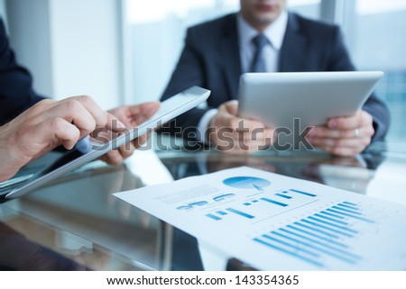Close-up of business partners using touchpads