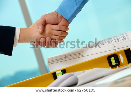 Close-up of business people handshaking over helmets, documents, worker tool - stock photo