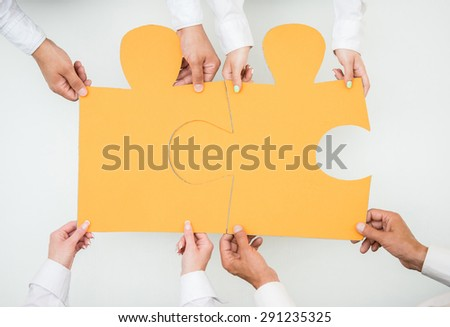 Close-up of business people holding two big piece of puzzle together. Team work. - stock photo