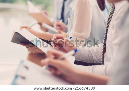 Close-up of business people making notes during the meeting - stock photo