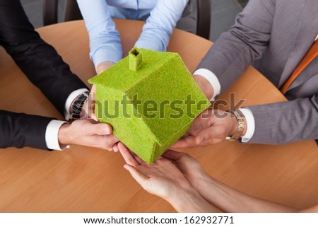 Close-up Of Business People's Hand Holding Eco Friendly Green House Over Desk - stock photo