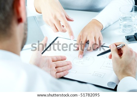 Close-up of business people sitting at the table and discussing  a new project - stock photo