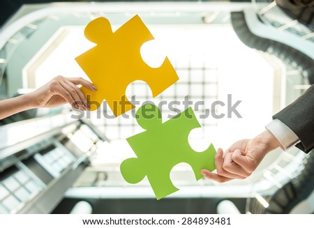 Close-up of business people wanting to put two pieces of puzzle together. - stock photo