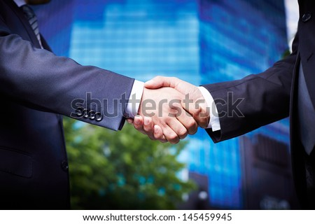 Close-up of business people welcoming each other in the downtown - stock photo