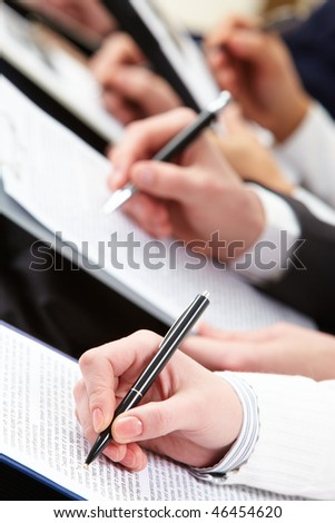 Close-up of business person hand making notes at lecture