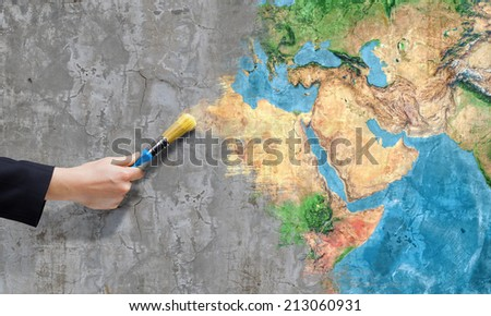 Close up of business person hand painting Earth planet. Elements of this image are furnished by NASA - stock photo