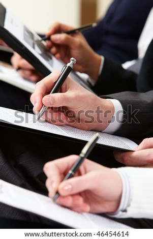 Close-up of business person hand with documents writing at lecture