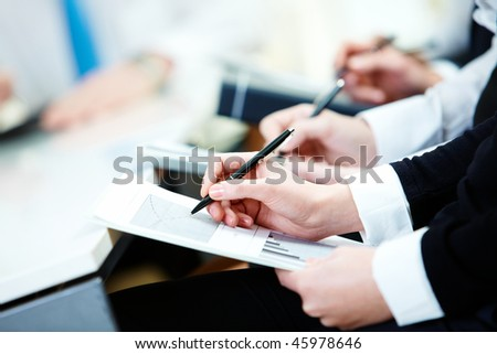 Close-up of business person hands with document writing at lecture