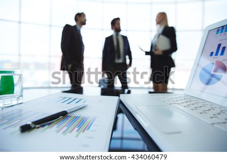 Close-up of business plan with people working in the background