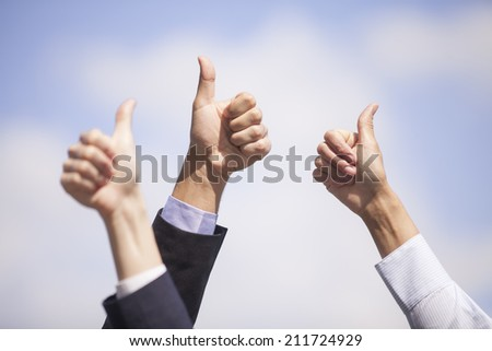 Close-up of business team holding their thumbs up. several human hands showing thumbs up against clear blue sky - stock photo