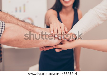 Close-up of business team putting their hands on top of each other - stock photo