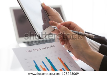 Close-up of  business team using digital tablet with financial diagram