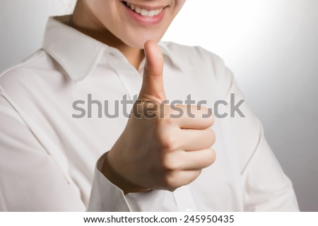 Close up of business woman smiling with thumb up. - stock photo