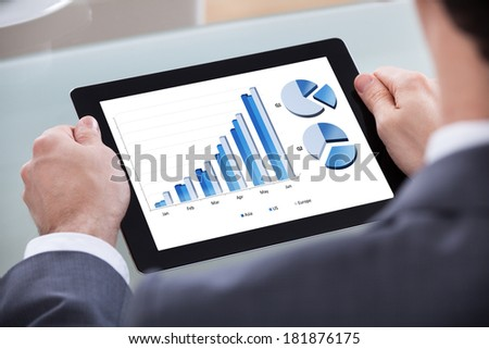 Close-up Of Businessman Analyzing Chart On Digital Tablet - stock photo