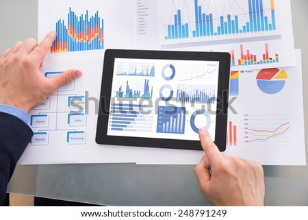 Close-up Of Businessman Analyzing Graph On Digital Tablet Kept Over Documents