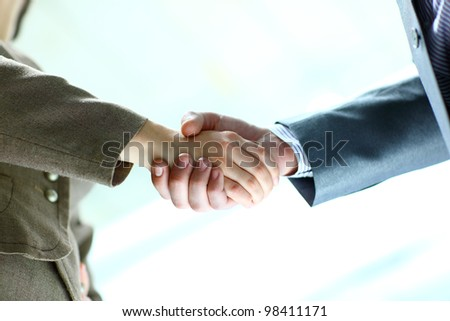 Close-up of businessman and businesswoman shaking hands - stock photo