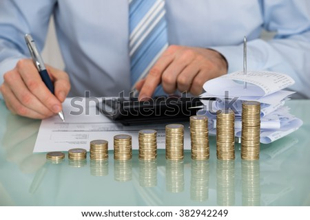 Close-up Of Businessman Calculating Bills In Front Of Stacked Coins - stock photo
