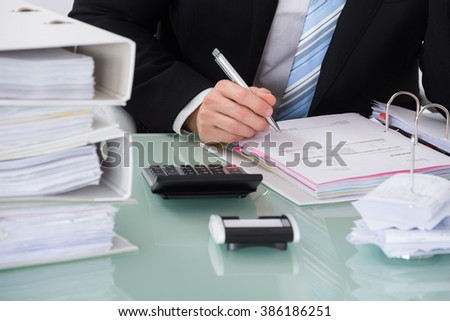 Close-up Of Businessman Calculating Invoice In Office