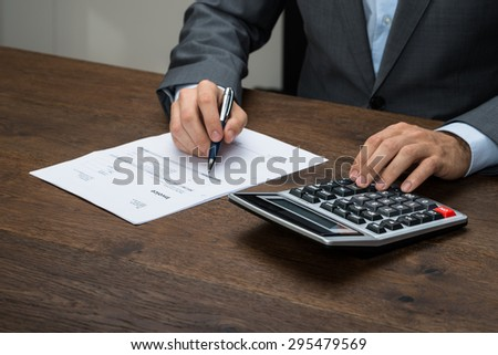 Close-up Of Businessman Calculating Invoice With Calculator At Desk - stock photo
