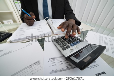 Close-up Of Businessman Calculating Invoices Using Calculator - stock photo