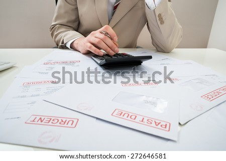 Close-up Of Businessman Calculating With Calculator Unpaid Bills - stock photo