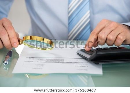 Close-up Of Businessman Checking Invoice With Magnifying Glass At Desk - stock photo