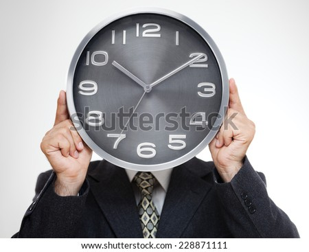 Close up of businessman covering his face with analog clock isolated on gray background - stock photo