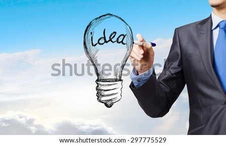 Close up of businessman drawing idea light bulb - stock photo